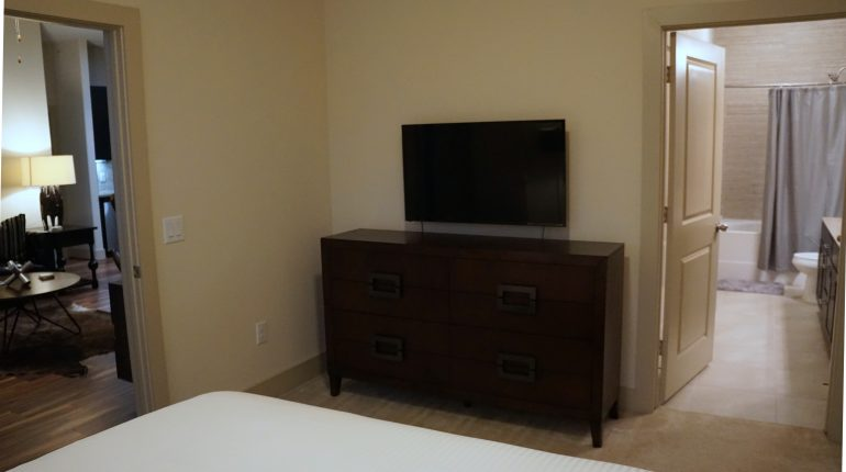 Nightstand view of master bedroom with queen size bed from the Texas Design at Premier Patient Housing.