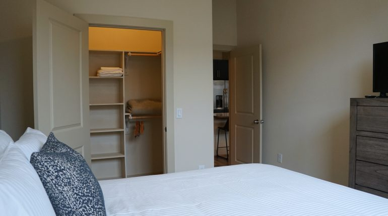 Low doorway view of bedroom with queen size bed from the Texas Design at Premier Patient Housing.