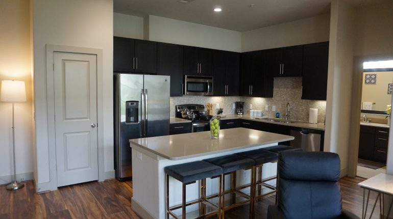 Full kitchen with fridge, oven, microwave and dining are on the island, from the Texas design at Premier Patient Housing.